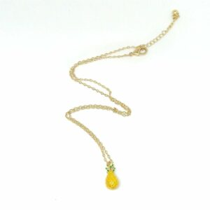 Gold tone chain necklace with an enamel pineapple charm