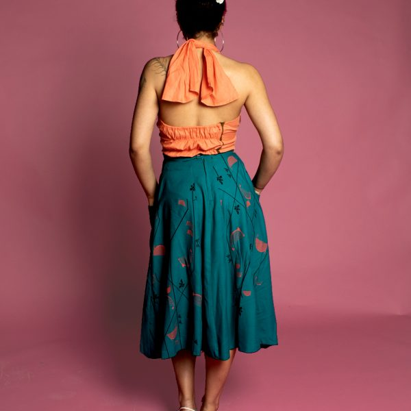 Back view of rockabilly halt top and 50s style flared skirt with pockets and boarder print, circle skirt with pockets