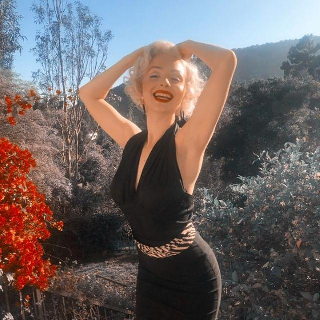 Pin up girl, Marylin Monroe lookalike. wearing a red lip, smiling with her hands on her head with blue sky in the background